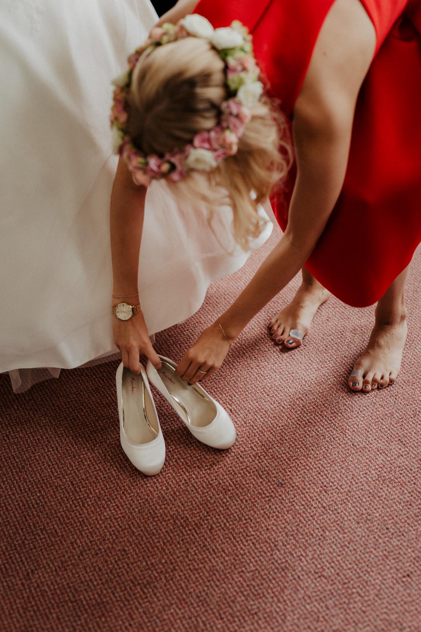 Trauzeugin hilft Braut in ihre Schuhe