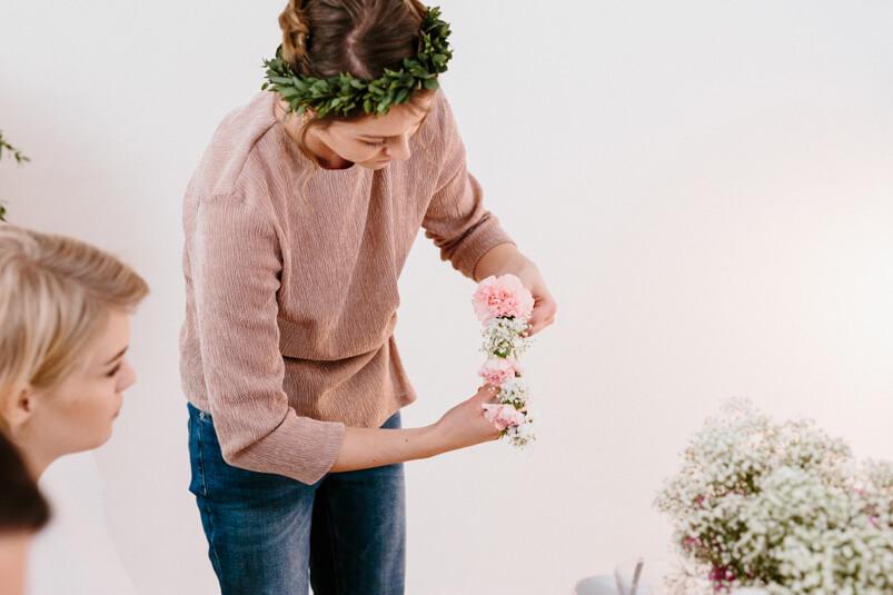 Kurleiterin erklärt wie man Blumenkränze bindet