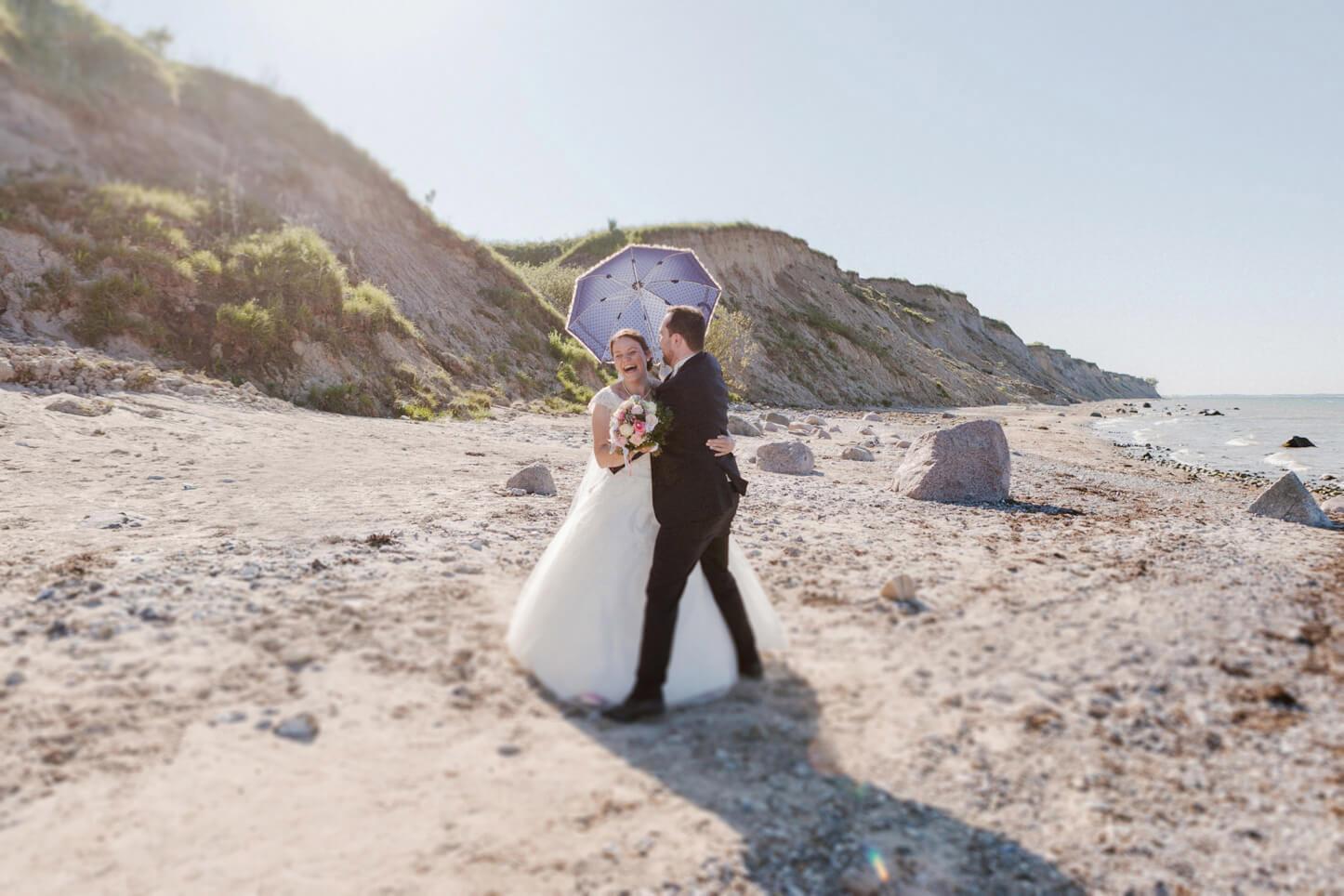 lachendes Brautpaar mit Sonnenschirm am Strand