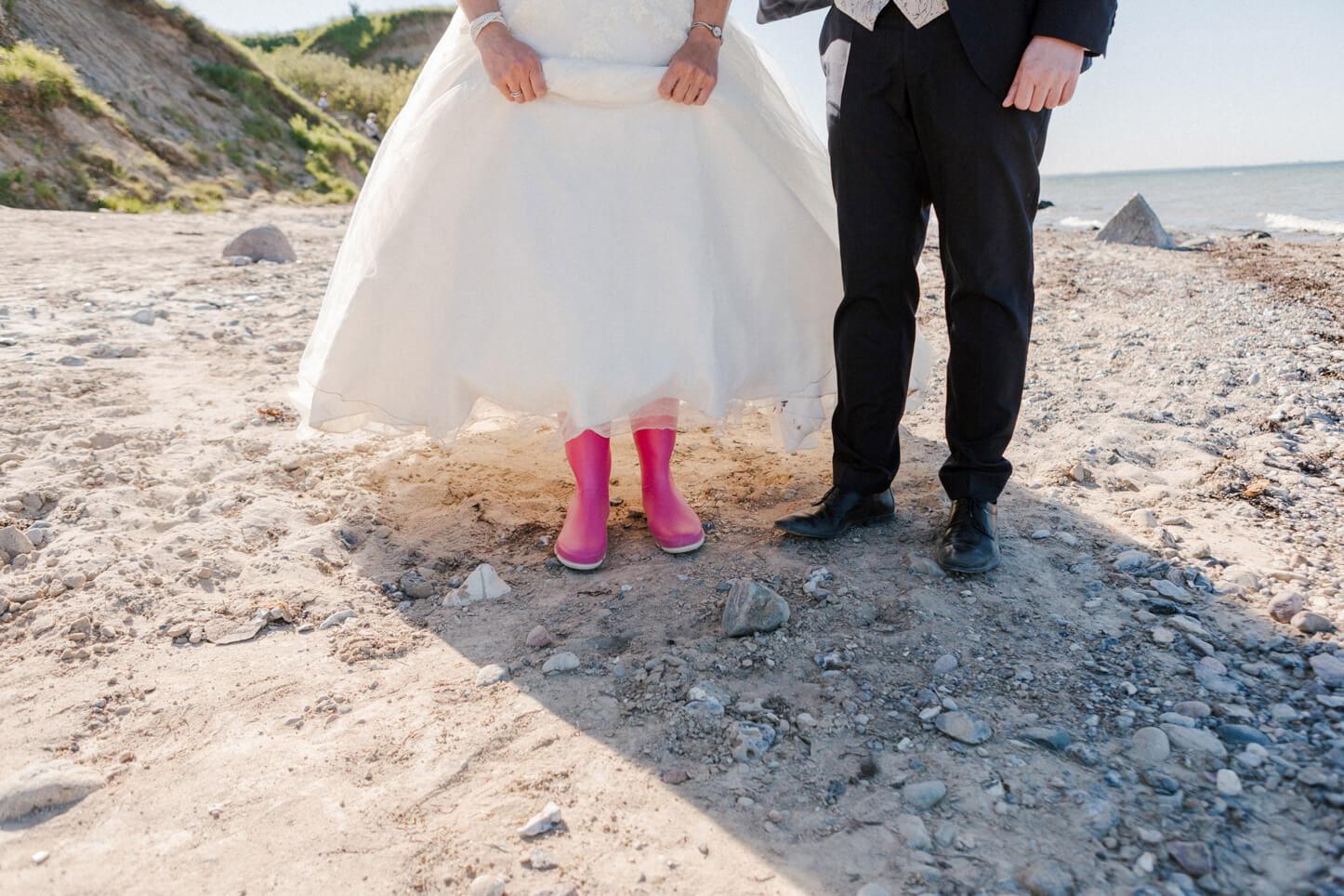 Braut mit rosa Gummistiefeln am Strand