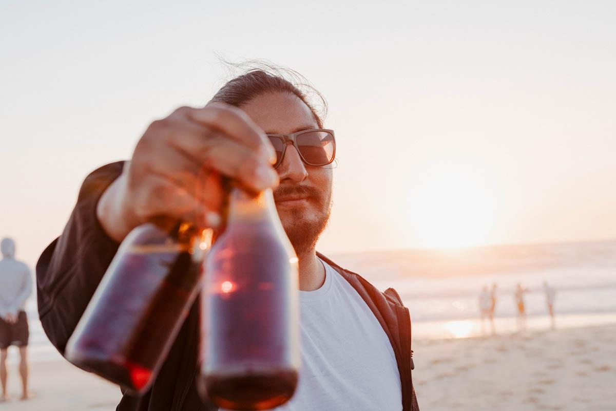 Junger Mann hält kaltes Bier in die Kamera