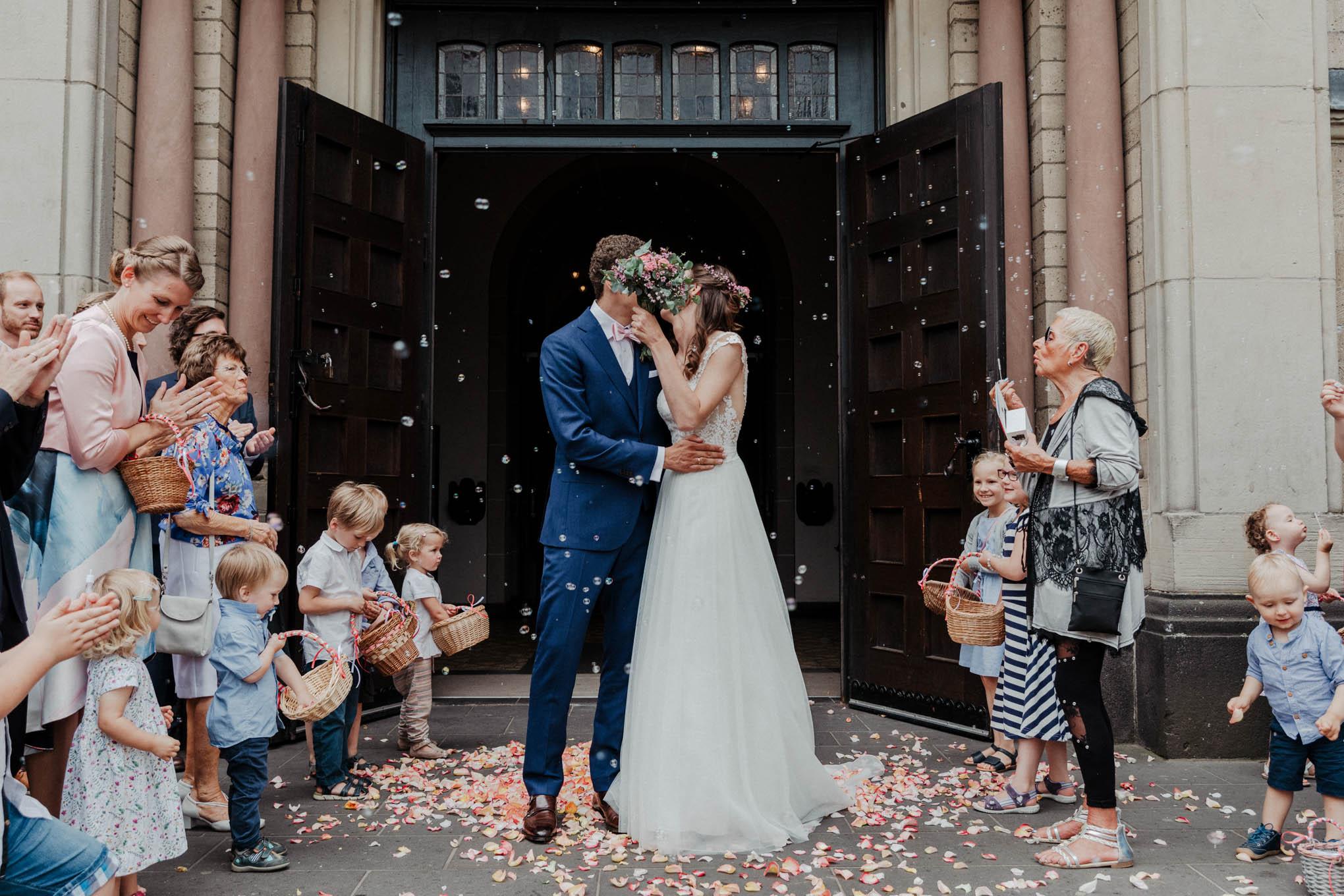 Brautpaar mit Konfetti vor Kirche