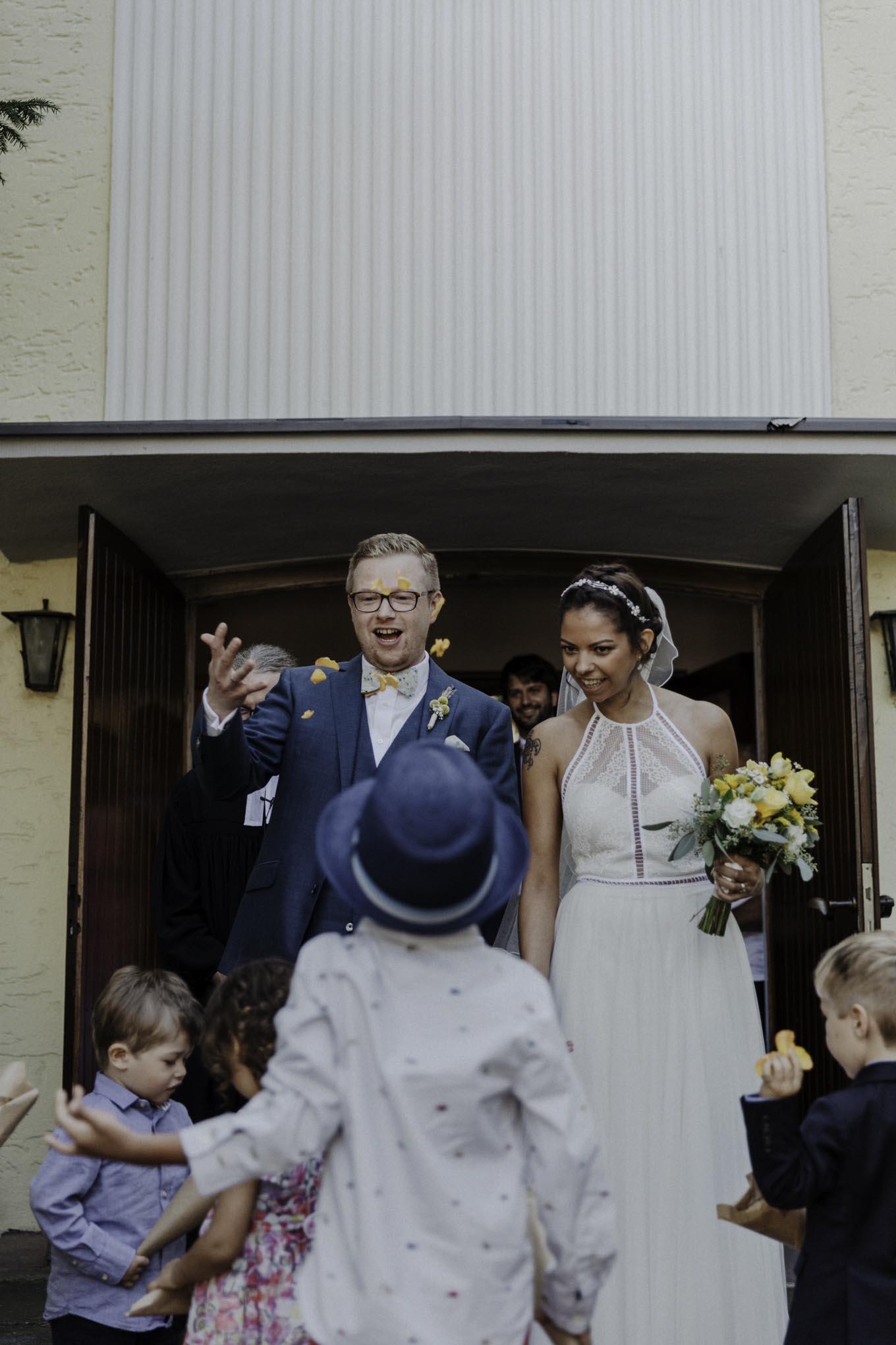 Brautpaar vor Kirche mit Blütenblättern