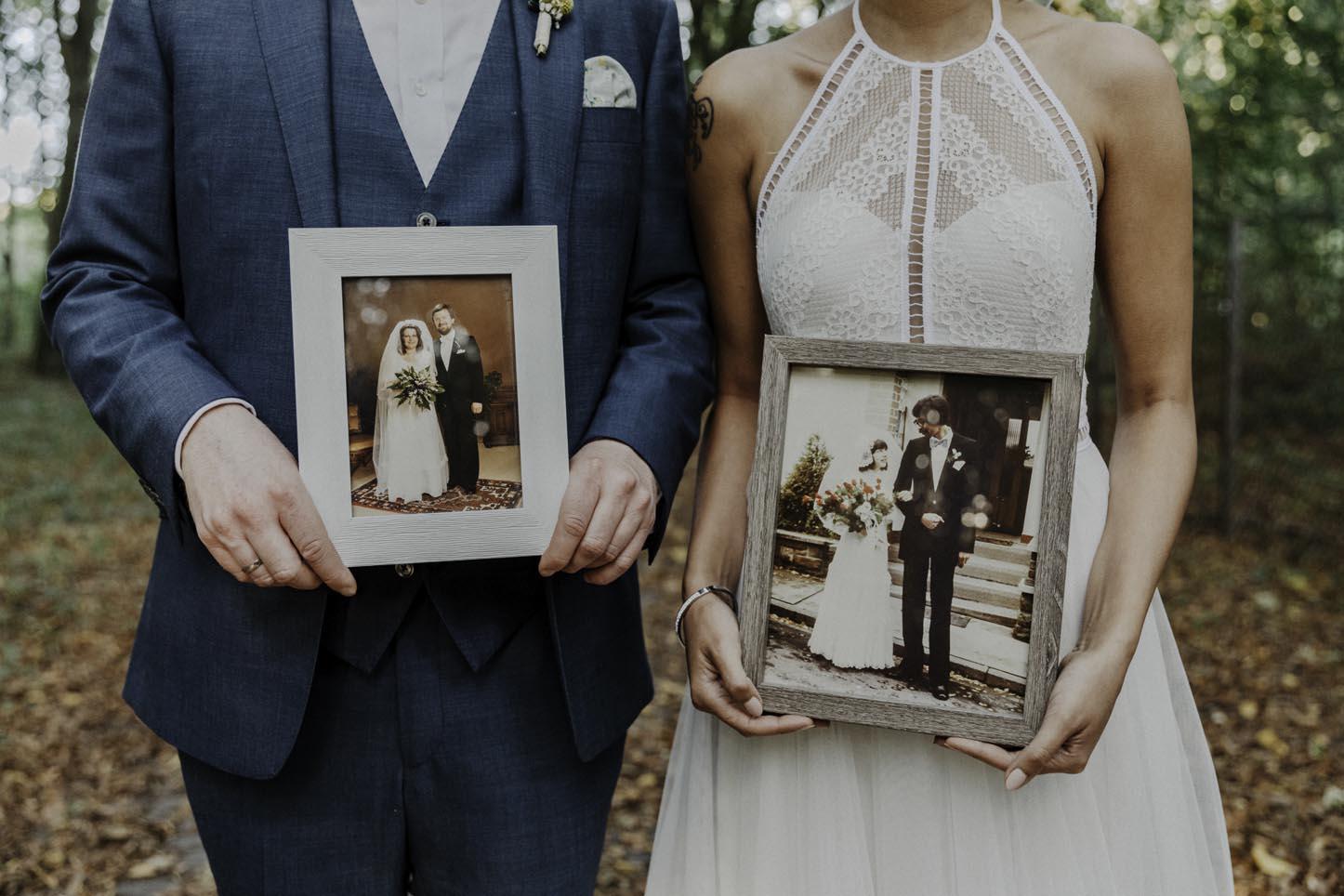 Brautpaar mit Hochzeitsfotos der Eltern