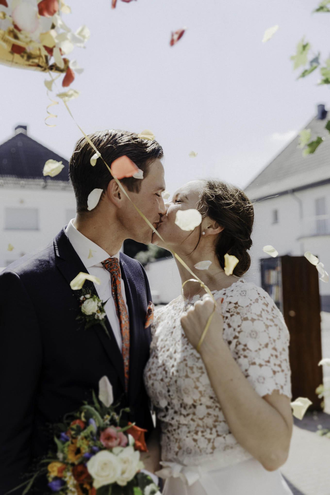 Küssendes Brautpaar mit Blüten und Luftballon