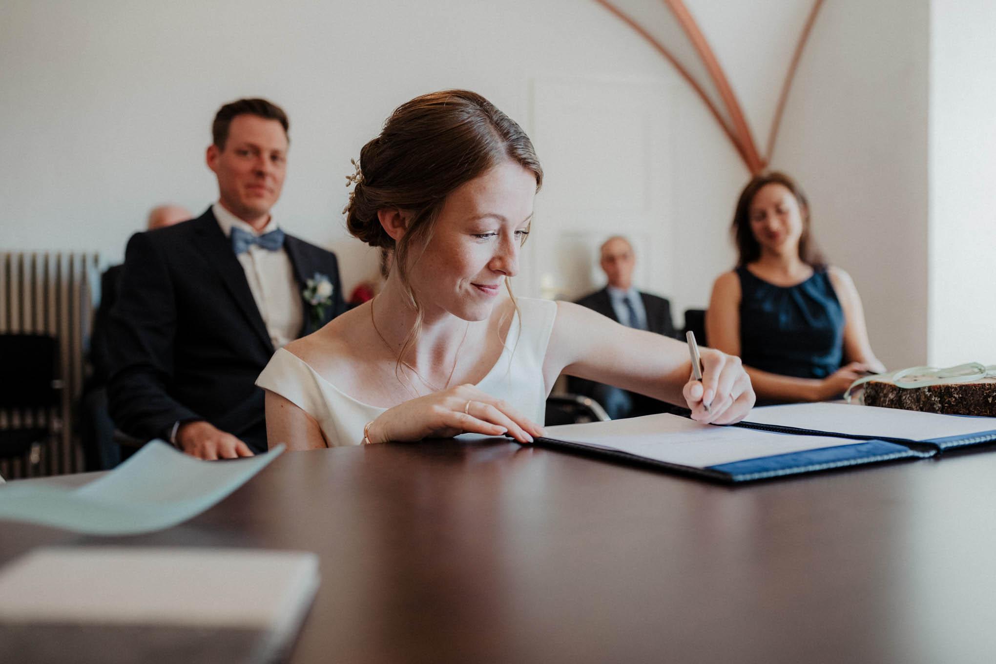 Braut unterschreibt im Standesamt