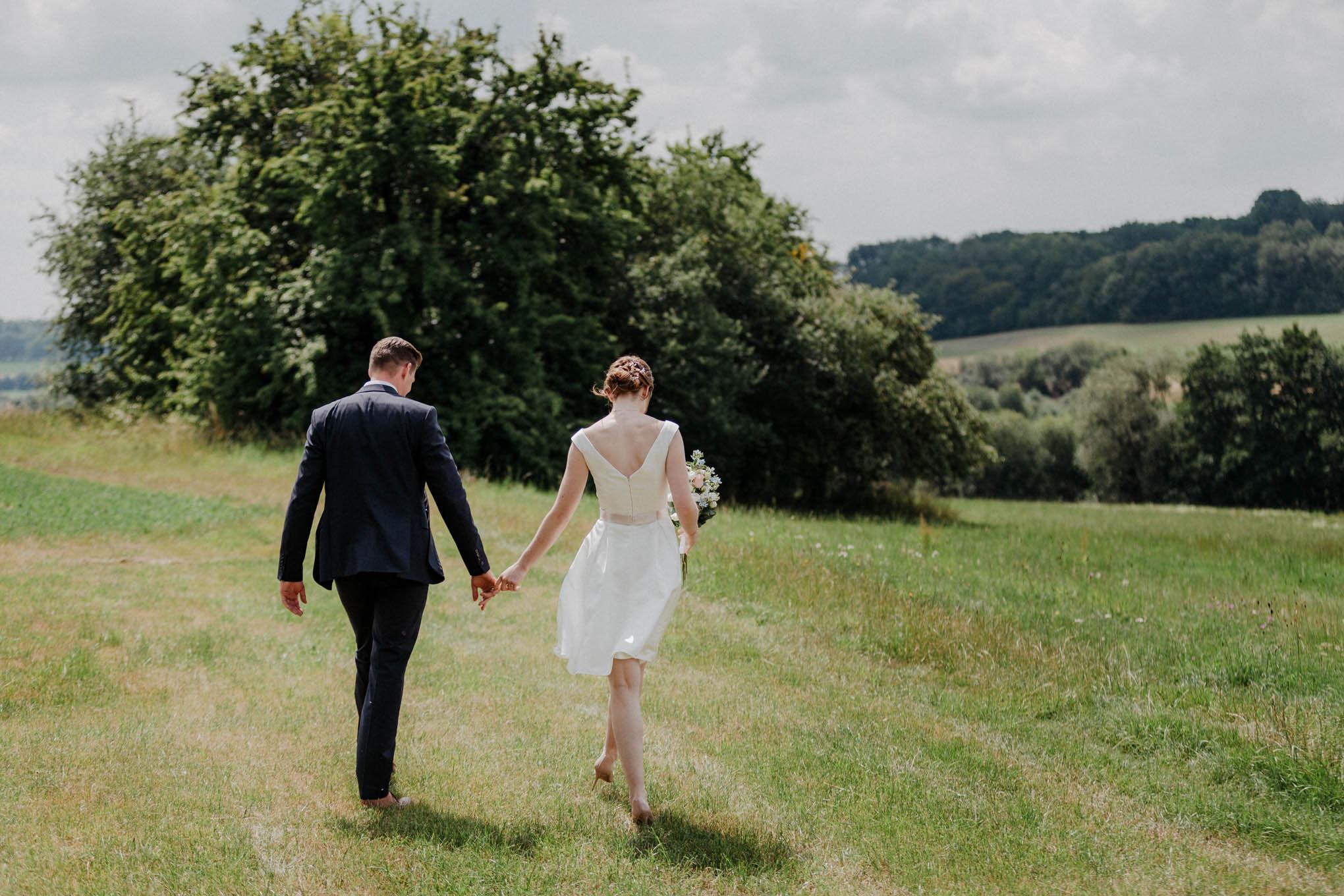Brautpaar Hand in Hand auf dem Feld im Westerwald