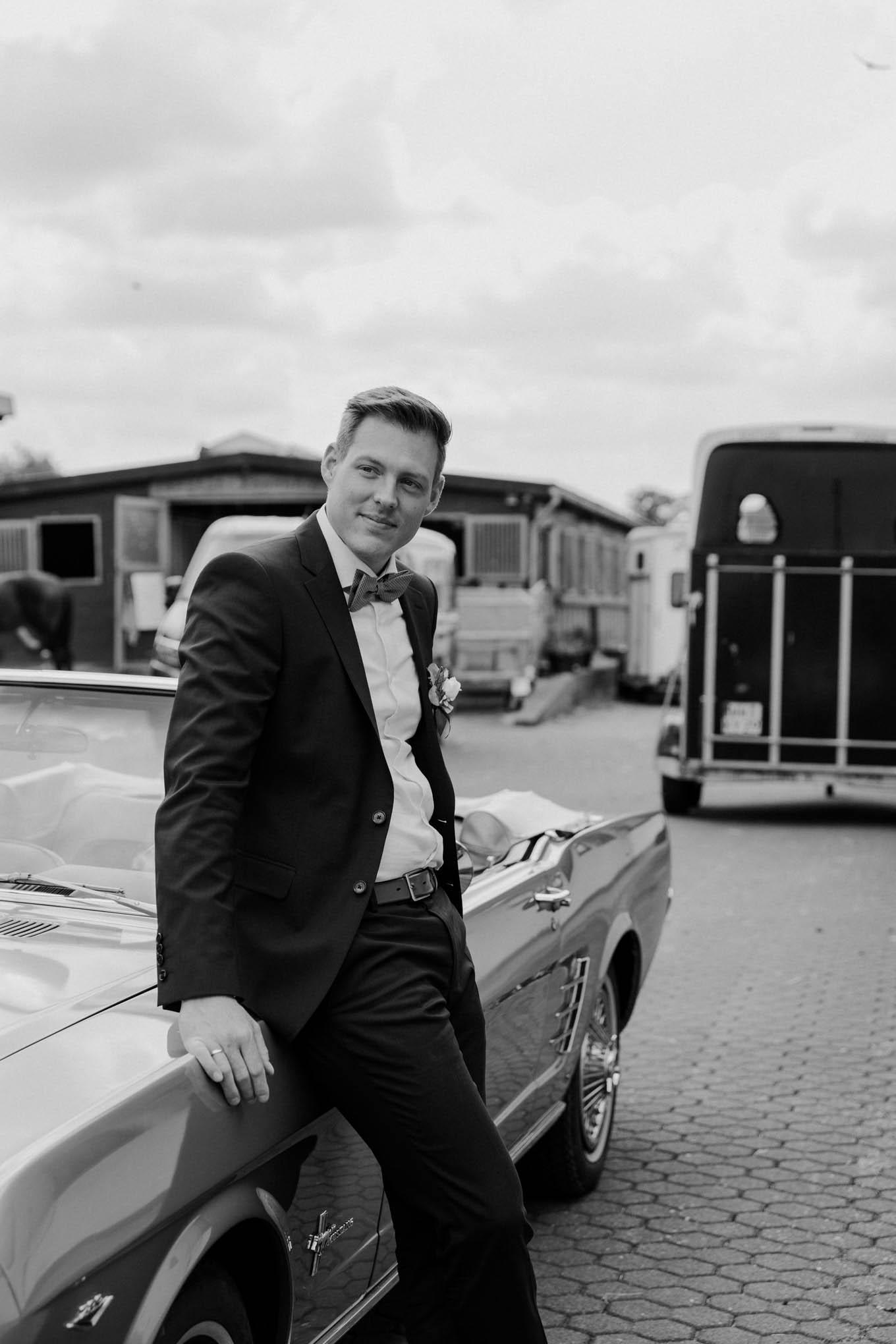 Bräutigam angelehnt an Ford Mustang